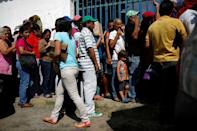 Zulay Pulgar (C), 43, stands in line outside a hardware store, next to her son Emmanuel, 4, to buy cement and resell it in Punto Fijo, Venezuela November 17, 2016. Picture taken November 17, 2016. REUTERS/Carlos Garcia Rawlins