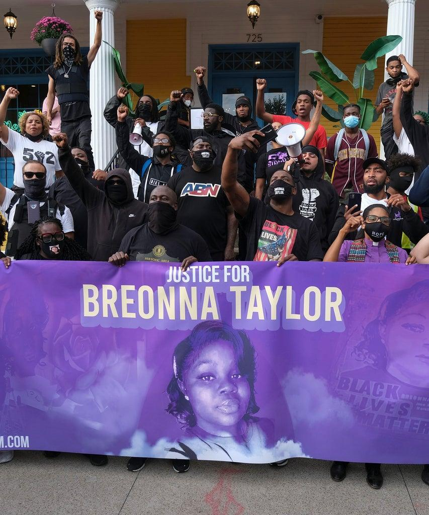TOPSHOT – Demonstrators pose for a photo in front of a local restaurant in the NULU neighborhood on a third day of protest over the lack of criminal charges in the police killing of Breonna Taylor and the result of a grand jury inquiry, in Louisville, Kentucky, on September 25, 2020. – The family of Breonna Taylor today, September 25, demanded that US authorities release grand jury transcripts showing why no police will face direct criminal charges over her death, which has once again galvanized protesters angry about racism and police brutality in America. (Photo by Jeff Dean / AFP) (Photo by JEFF DEAN/AFP via Getty Images)
