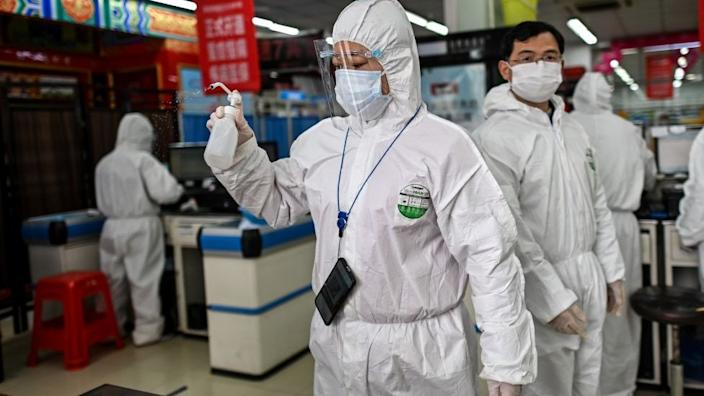 A woman wearing a protective suit sprays disinfectant in a pharmacy in Wuhan, in China's central Hubei province on March 30, 2020