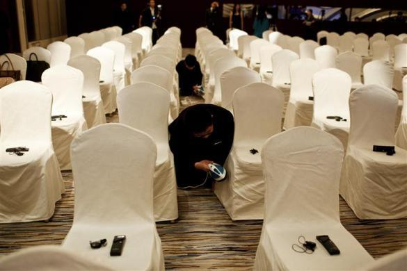 Employees use irons on chair covers before a Louis Vuitton's news conference in Shanghai, July 18, 2012.