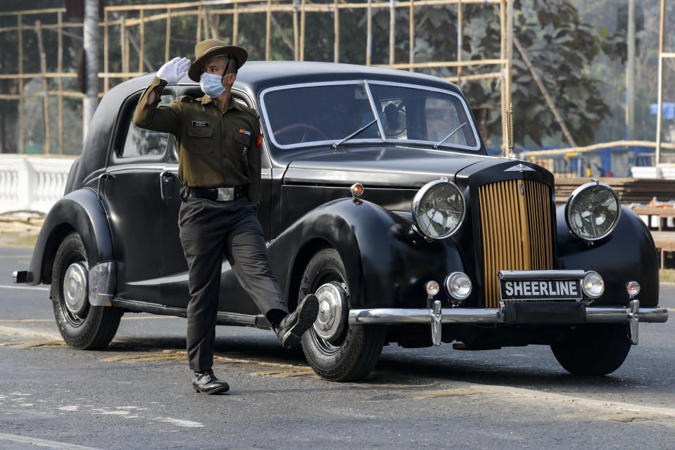 An Indian army soldier wearing a face mask to prevent the spread of the coronavirus marches alongside a vintage 1940 Austin A125 Sheerline car during rehearsals for Republic Day parade in Kolkata, India, Friday, Jan. 22, 2021. (AP Photo/Bikas Das)