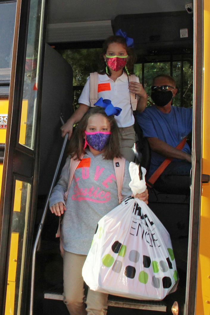 Masked students arrive at Newton County Elementary School in Decatur, Miss., on Aug. 3.  Thousands of students across the nation are set to resume in-person school for the first time since March. Parents have to balance the children's need for socialization and instruction that school provides with the risks of coronavirus.