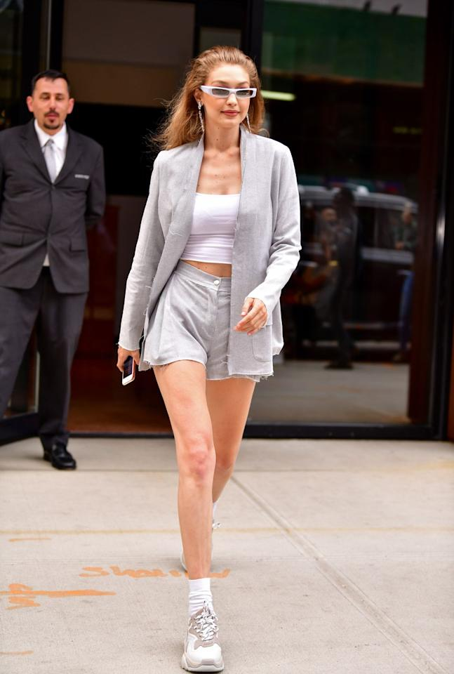 "<p>Hadid left her New York City apartment to attend The Art of the Mix event at ABC Cocina. For the party, she wore a gray blazer and shorts set by Sydney-based womenswear label Pfeiffer. The model accessorized with chunky Ash sneakers, Alexandre Vauthier x Alain Mikli sunglasses, and <a rel=""nofollow"" href=""https://www.marieclaire.com/fashion/g21951111/celebrites-affordable-jewelry/"">surprisingly cheap</a> BaubleBar earrings.</p>"