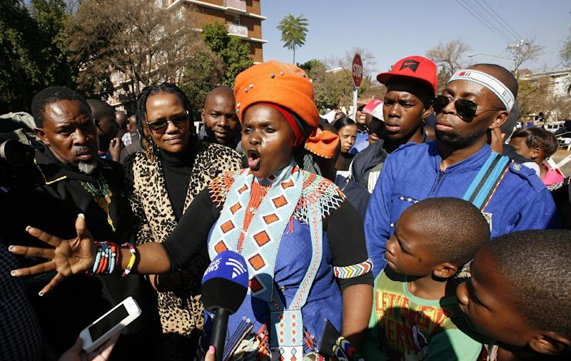 Jessica Mbangeni, center, performs a poem for former South African President Nelson Mandela outside the Mediclinic Heart Hospital where is being treated in Pretoria, South Africa Monday, July 1, 2013. Former president Nelson Mandela remained in a critical condition on Monday. (AP Photo/Themba Hadebe)