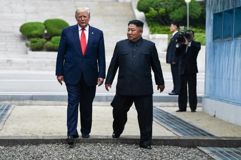 North Korea's leader Kim Jong Un and US President Donald Trump cross south of the Military Demarcation Line that divides North and South Korea, after Trump briefly stepped over to the northern side in June 30, 2019
