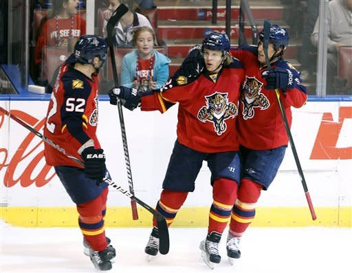 Florida Panthers right wing Kris Versteeg, center, celebrates a goal with defenseman Jason Garrison, left, and center Stephen Weiss, right, during the second period of an NHL hockey game against the New Jersey Devils, Tuesday, Dec. 13, 2011, in Sunrise, Fla. (AP Photo/Wilfredo Lee)