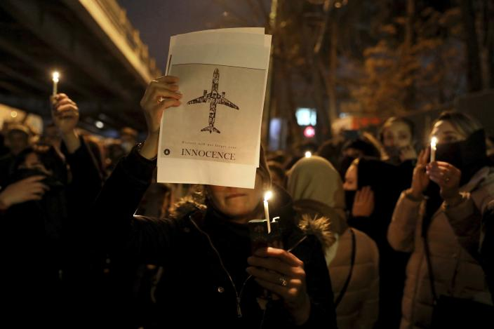 FILE - In this Jan. 11, 2020 file photo, people gather for a candlelight vigil to remember the victims of the Ukraine plane crash, at the gate of Amri Kabir University in Tehran, Iran. More questions than answers remain about the disaster that killed 176 people on board the Ukrainian jetliner, a year after Iran's military mistakenly downed the plane with surface-to-air missiles. Officials in Canada, which was home to many of the passengers on the doomed plane, and other affected countries have raised concerns about the lack of transparency and accountability in Iran's investigation of its own military. (AP Photo/Ebrahim Noroozi, File)
