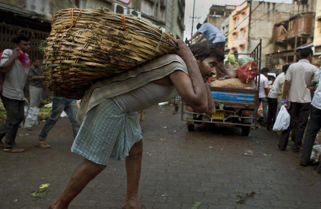 <p>An Indian laborer carries vegetables in a basket on his back at a vegetable market in Gauhati, India, Sunday, May 21, 2017. (Photo: Anupam Nath/AP) </p>