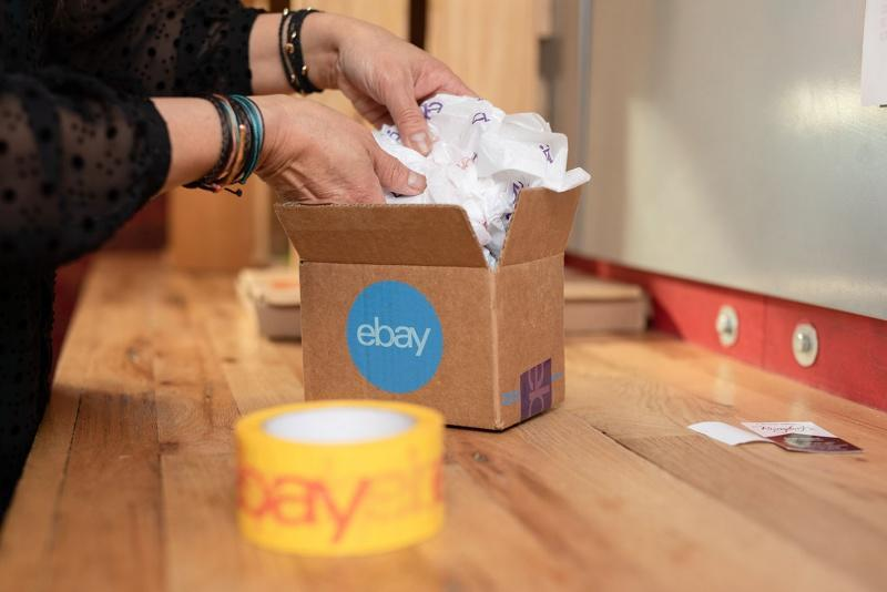 A person placing an item in an eBay branded carboard box.