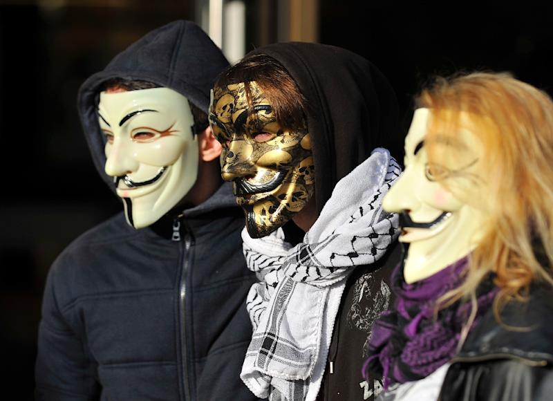 "The ""Anonymous"" hackers collective, represented here by mask-wearing demonstrators at a French trial November 9, 2015, claimed November 17 to have taken down 5,500 Twitter accounts tied to the Islamic State jihadist group"