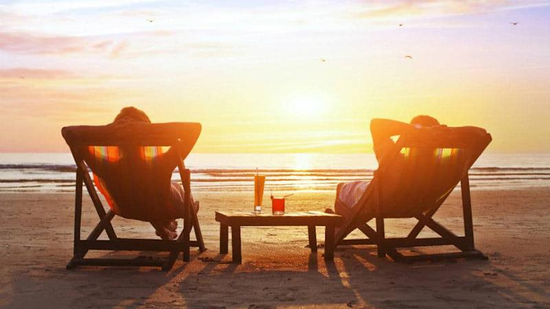 Couple relaxing on a beach in front of a sunset