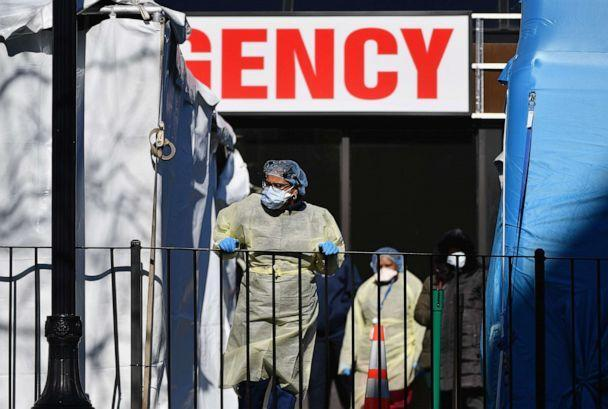 PHOTO: Medical workers stand outside at Elmhurst Hospital Center in the Queens borough of New York City on March 26, 2020. (Angela Weiss/AFP via Getty Images)