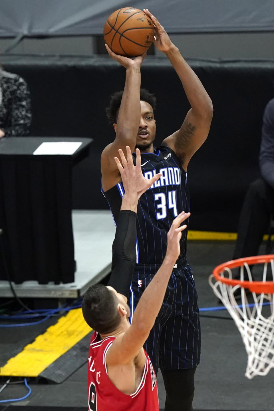 Orlando Magic center Wendell Carter Jr., top, shoots against Chicago Bulls center Nikola Vucevic during the first half of an NBA basketball game in Chicago, Wednesday, April 14, 2021. (AP Photo/Nam Y. Huh)