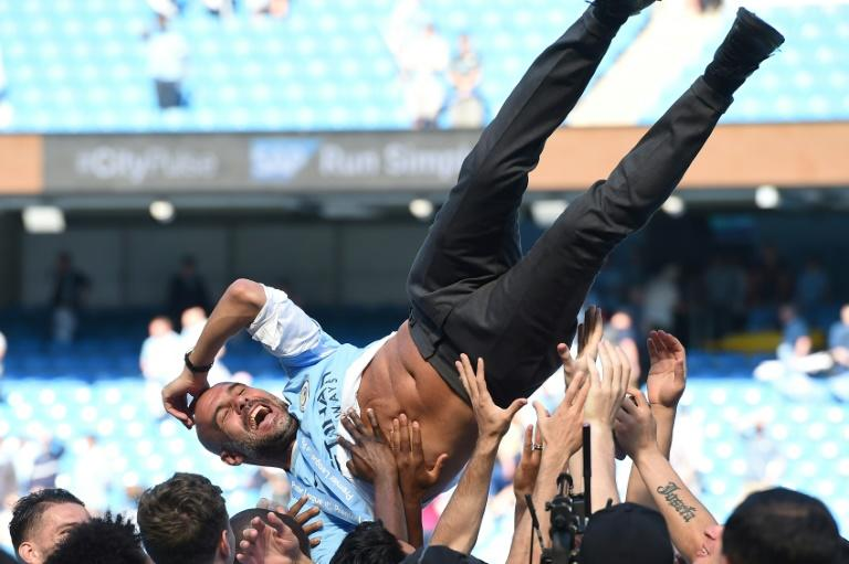 City on top: Jubilant players lift Pep Guardiola in celebration of their Premier League title