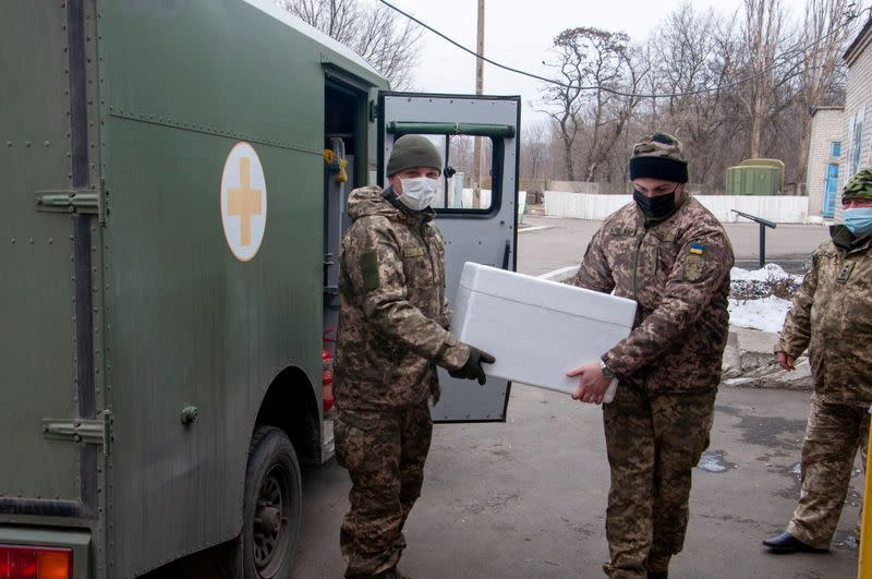FILE PHOTO: Ukrainian servicemen carry a box with the Oxford-AstraZeneca vaccine in Donetsk Region