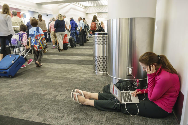 A woman sat on the floor in Los Angeles, LAX, international airport charging her laptop. (Photo by: Jeffrey Greenberg/Universal Images Group via Getty Images)