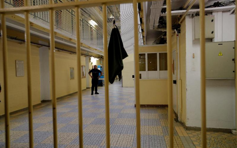 A guard stands in the corridor of the Fresnes prison, south of Paris - AP