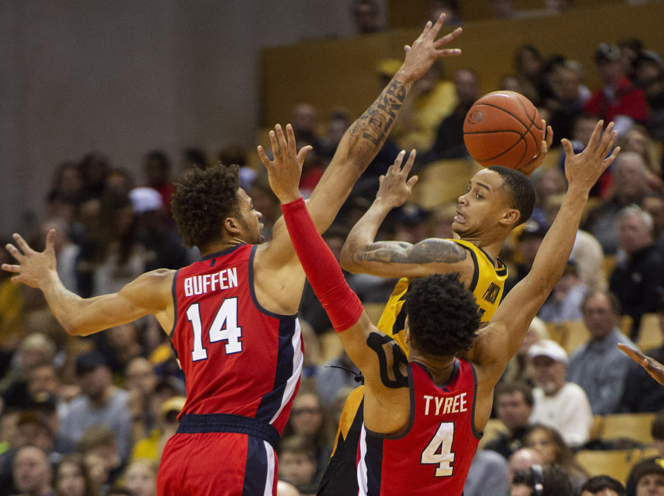 Missouri's Xavier Pinson, right, passes the ball as he is defended by Mississippi's KJ Buffen, left, and Breein Tyree, center, during the second half of an NCAA college basketball game Saturday, March 9, 2019, in Columbia, Mo. Mississippi won the game 73-68. (AP Photo/L.G. Patterson)
