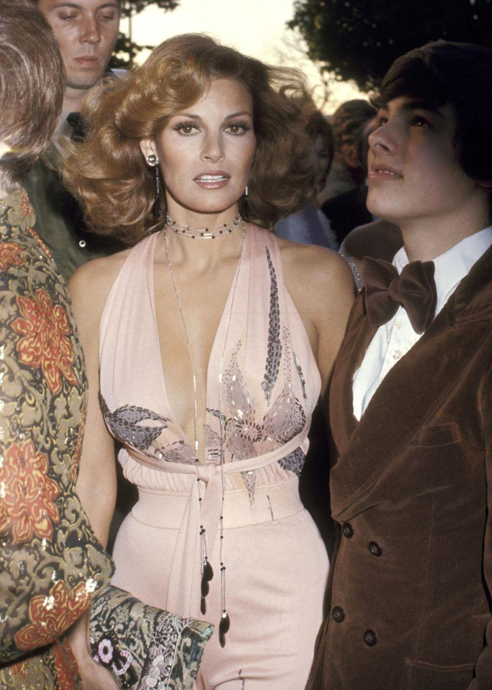 <p>Add together a haltered pink jumpsuit, a plunging neckline, and a wrap necklace, and you get one of the hottest Oscars looks of all time. The actress presented the award for Best Feature-Length Documentary that year.</p>