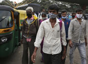 Indian commuters wearing face mask as a precaution against the coronavirus arrive at a bus station in Bengaluru, India, Tuesday, Jan. 5, 2021. India authorized two COVID-19 vaccines on Sunday, paving the way for a huge inoculation program to stem the coronavirus pandemic in the world's second most populous country. (AP Photo/Aijaz Rahi)