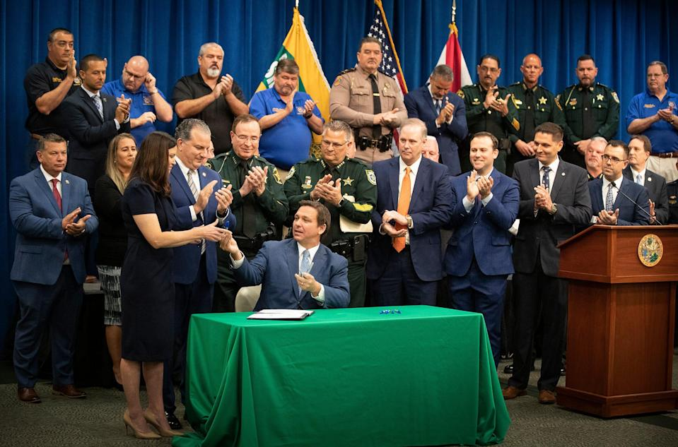 Florida Governor Ron Desantis hands a blue sharpie to Florida Attorney General Ashley Moody  after he signed a bill Combating Public Disorder during a signing ceremony at the Polk County Sheriff's Operation Center in Winter Haven Fl. Monday April 19 2021.  ERNST PETERS/ THE LEDGER