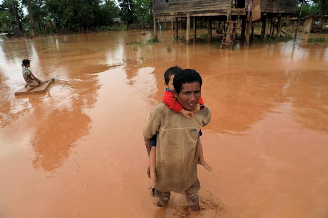 <p>A man carries his child during the flood after the Xepian-Xe Nam Noy hydropower dam collapsed in Attapeu province, Laos, July 26, 2018. (Photo: Soe Zeya Tun/Reuters) </p>