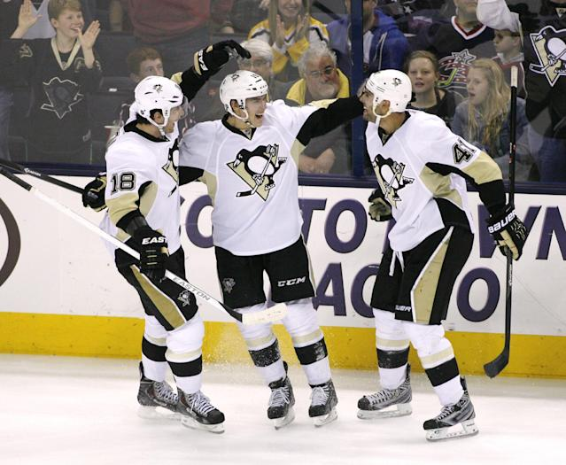 Pittsburgh Penguins' Beau Bennett (19), center, celebrates with teammates James Neal (18) and Robert Bortuzzo (41) after scoring to make it 2-0 during the third period of an NHL hockey game, Friday, March 28, 2014, in Columbus, Ohio. (AP Photo/Mike Munden)