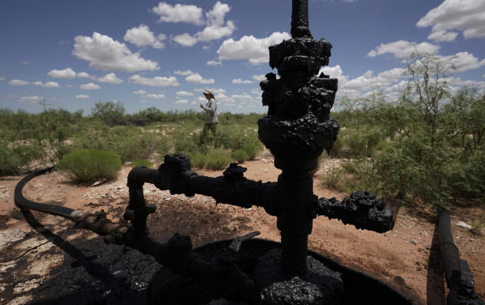 Ashley Williams Watt walks near a wellhead and flowline at her ranch, Friday, July 9, 2021, near Crane, Texas. The wells on Watt's property seem to be unplugging themselves. Some are leaking dangerous chemicals into the ground, which are seeping into her cattle's drinking water. And she doesn't know how long it's been going on. (AP Photo/Eric Gay)