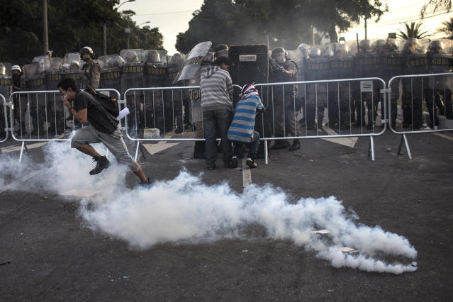 People run from tear gas fired by police as they protest outside the Minerao stadium where a Confederations Cup soccer match takes place between Japan and Mexico in Belo Horizonte, Brazil, Saturday, June 22, 2013. Demonstrators once again took to the streets of Brazil on Saturday, continuing a wave of protests that have shaken the nation and pushed the government to promise a crackdown on corruption and greater spending on social services. (AP Photo/Felipe Dana)