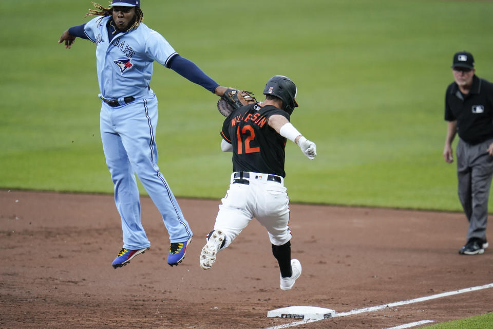 Toronto Blue Jays first base Vladimir Guerrero Jr., left, applies a tag on Baltimore Orioles' Stevie Wilkerson (12) for the out after going up to reach a throw from Blue Jays shortstop Marcus Semien during the third inning of a baseball game, Saturday, June 19, 2021, in Baltimore. (AP Photo/Julio Cortez)