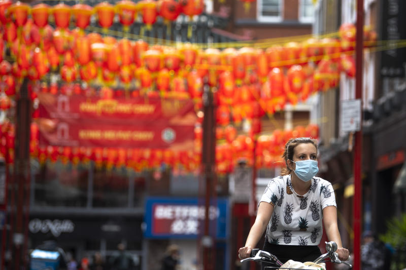 A woman wearing a face mask cycles through Chinatown, central London, as the UK continues in lockdown to help curb the spread of the coronavirus.