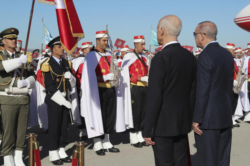 Turkey's President Recep Tayyip Erdogan, right, and Tunisian President Kais Saied review the honor guard at the airport, in Tunis, Tunisia, Wednesday, Dec. 25, 2019. Erdogan with top Turkish officials is on an unannounced visit to Tunisia to meet Saied. (Turkish Presidency via AP, Pool)