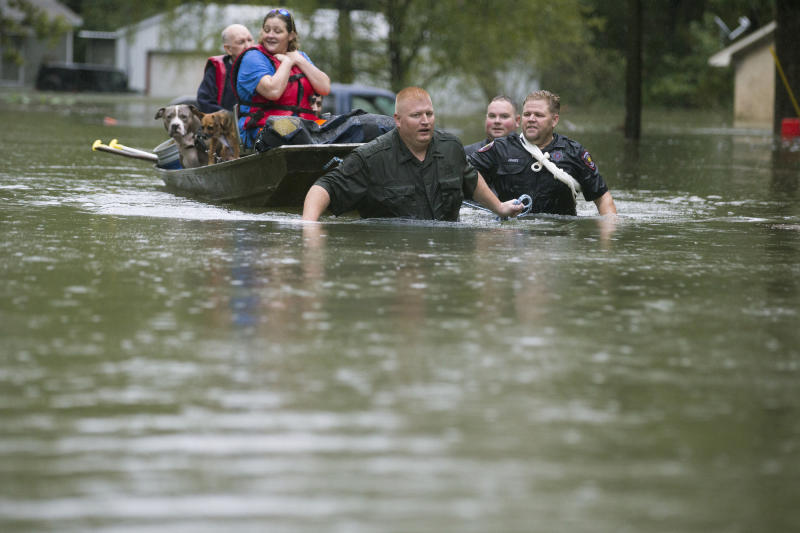 Splendora Police Lt. Troy Teller, left, Cpl. Jacob Rutherford and Mike Jones pull a boat carrying Anita McFadden and Fred Stewart from their flooded neighborhood inundated by rain from Tropical Depression Imelda on Thursday, Sept. 19, 2019, in Spendora, Texas. (Photo: Brett Coomer/Houston Chronicle via AP)