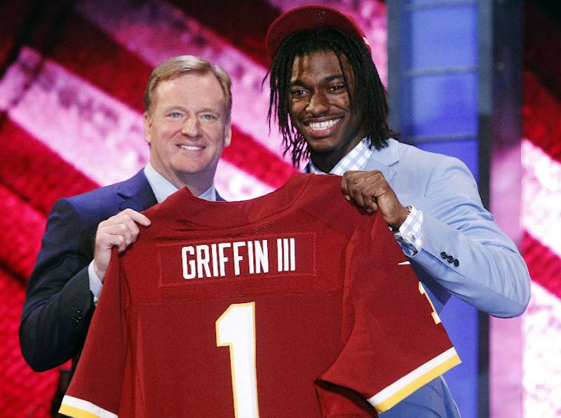 FILE - In this April 26, 2012, file photo, quarterback Robert Griffin III, right, poses for photographs with NFL Commissioner Roger Goodell after he was selected as the second pick overall by the Washington Redskins in the first round of the NFL football draft in New York. Fashionistas surely will be tracking the expensive, colorful designer suits, hairstyles (think dreadlocks) and even socks of the draftees as they take the stage after being selected. (Think Robert Griffin III, the Redskins' top pick in 2012, who wore a baby blue jacket, checkered-patterned shirt, purplish tie with horizontal stripes, and burgundy and gold socks. Fashion is one of the things to watch for during the three-day NFL draft beginning Thursday, April 25, 2013. (AP Photo/Jason DeCrow, File)