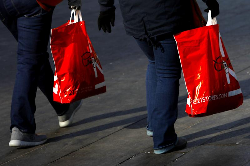 People carry shopping bags from Century 21 during a Black Friday. REUTERS/Andrew Kelly