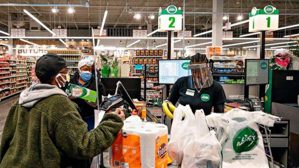 PHOTO: A cashier wearing a face shield bags groceries for a customer at the Local Market Foods store in Chicago, April, 8, 2020. (Kamil Krzaczynski/AFP via Getty Images, File)