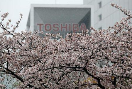The logo of Toshiba Corp is seen behind cherry blossoms at the company's headquarters in Tokyo
