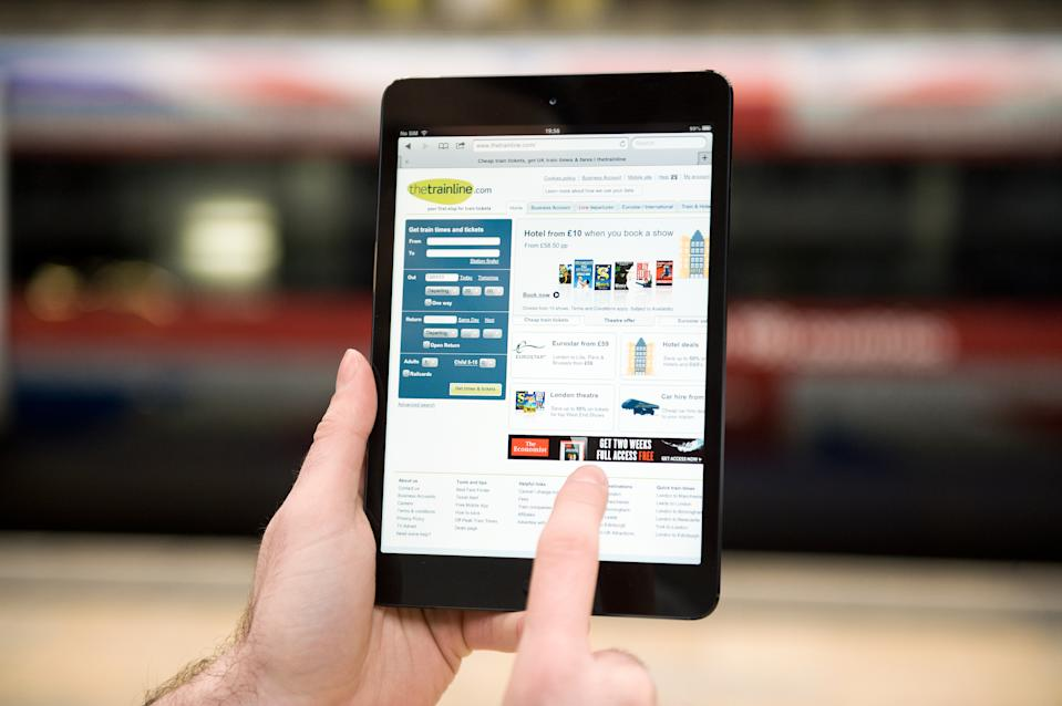 A close-up of a man accessing thetrainline.com on an Apple iPad Mini tablet computer at London's Paddington Station on January 14, 2013. Photo: Will Ireland/Future Publishing via Getty Images