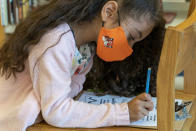 A first grader wears a face mask while doing work in the library during the coronavirus outbreak at the Post Road Elementary School, Thursday, Oct. 1, 2020, in White Plains, N.Y. (AP Photo/Mary Altaffer)