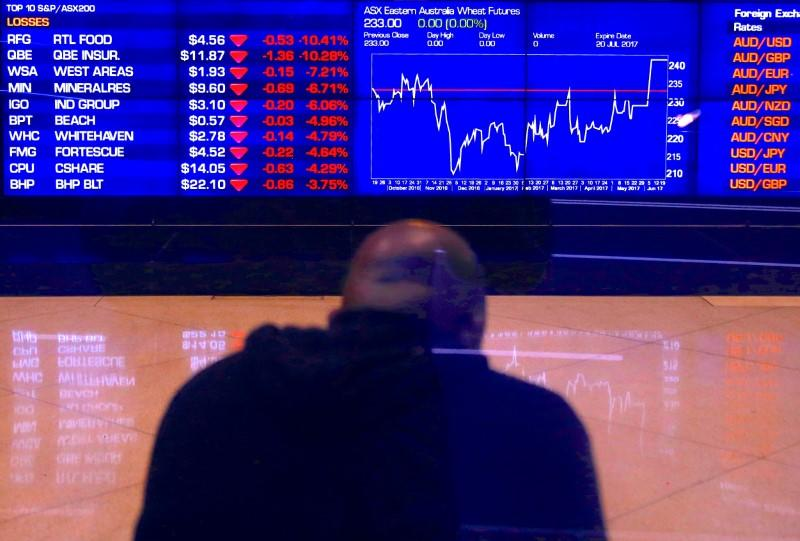 An investor sits in front of a board displaying stock prices at the Australian Securities Exchange in Sydney