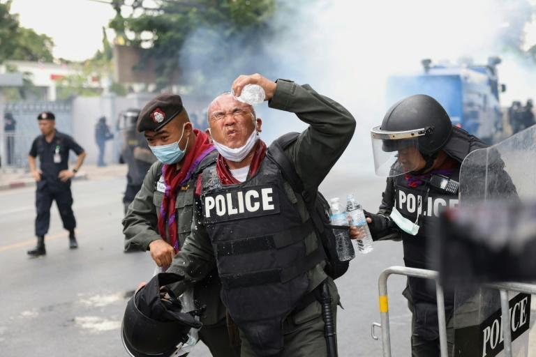 A policeman rinses tear gas from his eyes during the huge protest in Bangkok