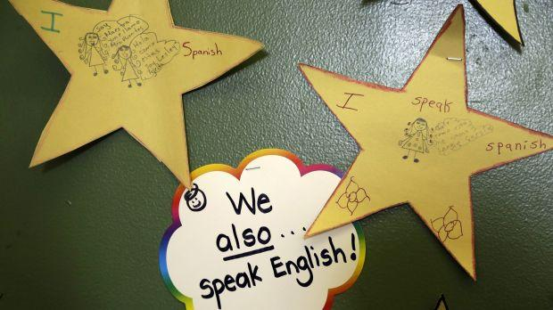 """A sticker reading, """"We also speak English"""" hangs on a classroom wall."""