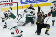 Vegas Golden Knights right wing Alex Tuch, right, celebrates after scoring against Minnesota Wild goaltender Cam Talbot (33) to tie the game in the final minute of the third period of an NHL hockey game Monday, March 1, 2021, in Las Vegas. (AP Photo/John Locher)