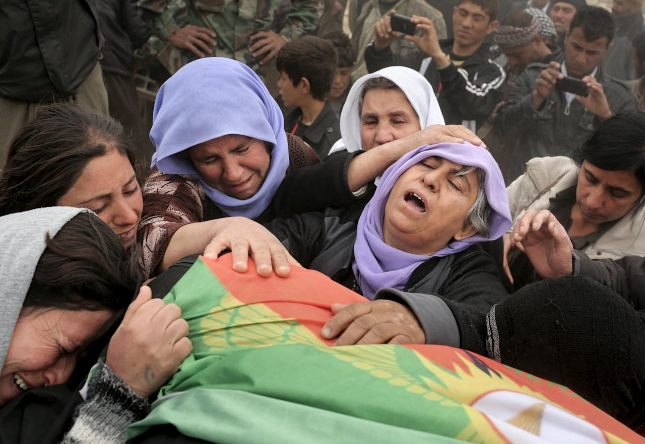 "ATTENTION EDITORS - VISUAL COVERAGE OF SCENES OF DEATH AND INJURY   The mother of a Yazidi fighter from YBS (2nd R), who was killed during fighting with Islamic State militants, mourns with relatives over the body of her son during a funeral ceremony at a cemetery in Sinjar, March 12, 2015. YBS are a Yazidi militant group, who are fighting against Islamic State. Women fighters at a PKK base on Mount Sinjar in northwest Iraq, just like their male counterparts, have to be ready for action at any time. Smoke from the front line, marking their battle against Islamic State, which launched an assault on northern Iraq last summer, is visible from the base. Many of the women have cut links with their families back home; the fighters come from all corners of the Kurdish region. REUTERS/Asmaa Waguih   PICTURE 12 OF 32 FOR WIDER IMAGE STORY ""KURDISH WOMEN BATTLE ISLAMIC STATE""  