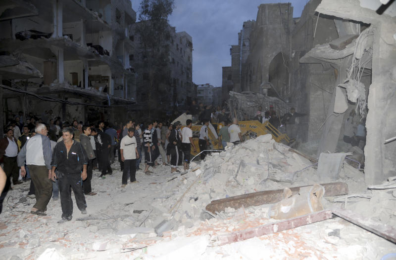 In this image released by the Syrian official news agency SANA , a crowd gather beneath the shattered facade of a building damaged by a car bomb in Damasus, Syria Friday Oct 26 2012. The blast in a residential area of Damascus, near a housing complex for police, killed five people and wounded more than 30, state TV said. A shaky holiday truce was marred by sporadic fighting and two car bombs Friday but gave war-battered Syrians a brief respite, allowing thousands of protesters to pour out of mosques to demand President Bashar Assad's ouster.(AP Photo/ Sana)