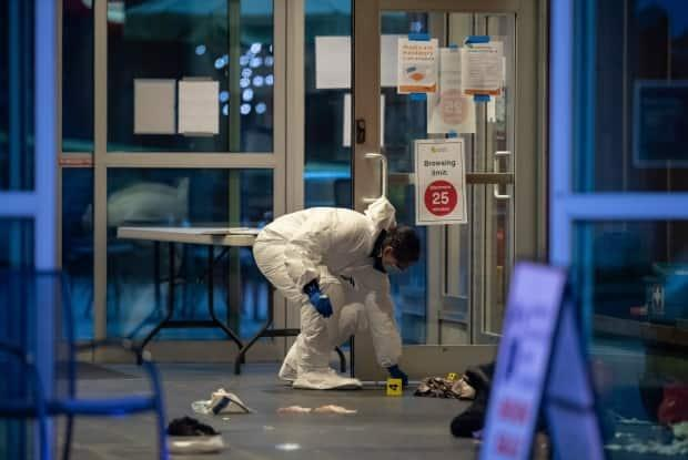 A forensics police officer collects evidence inside the Lynn Valley public library on Saturday.