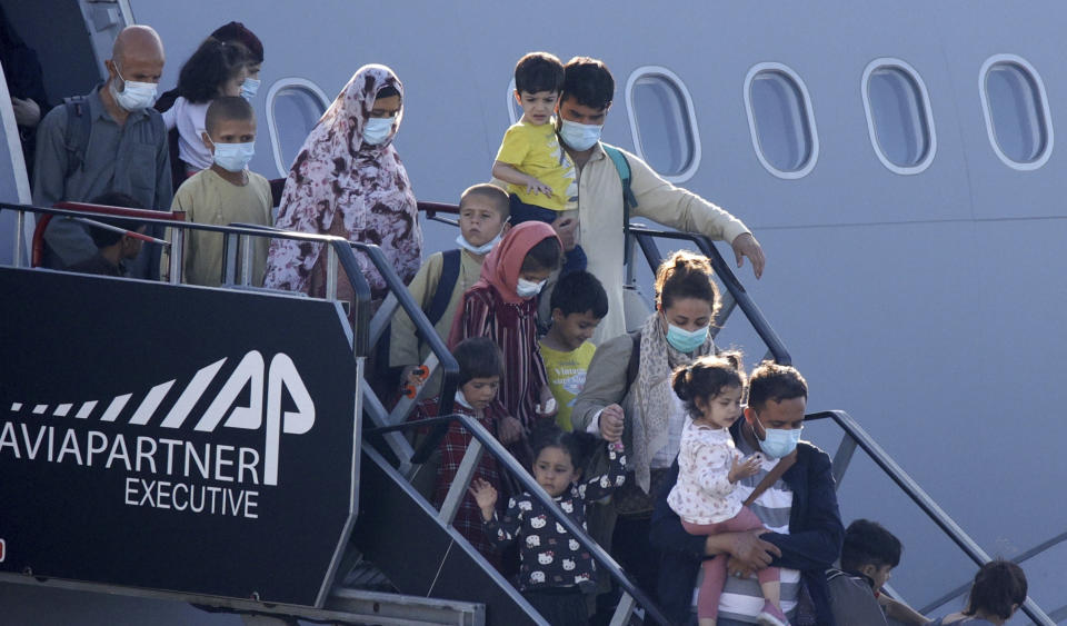People disembark from a Belgian military plane, after being evacuated from Afghanistan, as it arrives at Melsbroek Military Airport in Melsbroek, Belgium, Wednesday, Aug. 25, 2021. (AP Photo/Olivier Matthys)