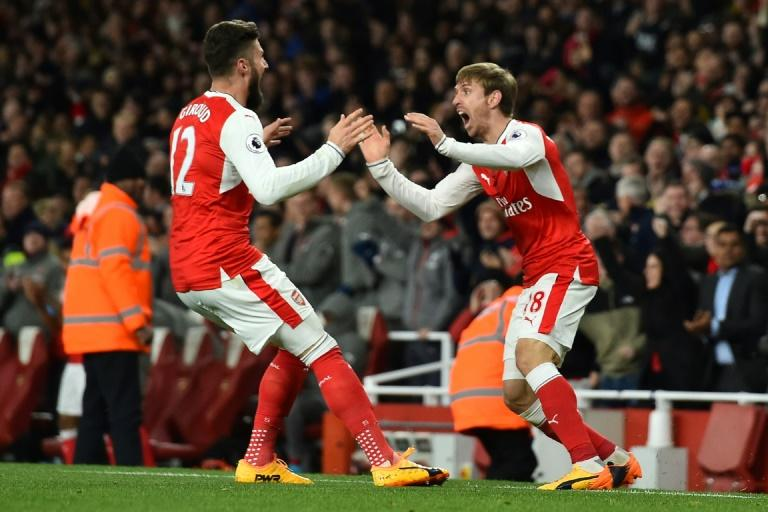 Arsenal's defender Nacho Monreal celebrates with Arsenal's striker Olivier Giroud (L) after his shot is deflected into the Leicester net by Leicester City' defender Robert Huth during the English Premier League football match April 26, 2017