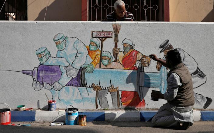 A man applies finishing touches to graffiti representing a vaccine, amidst the spread of coronavirus disease in Kolkata, India - Reuters