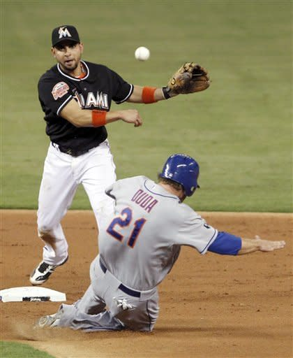 Miami Marlins second baseman Omar Infante, top, throws to first base for the double play as New York Mets' Lucas Duda (21) slides into second during the second inning of a baseball game on Friday, May 11, 2012, in Miami. Scott Hairston was out at first. (AP Photo/Wilfredo Lee)